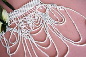 lirios blancos y un collar de perlas sobre un fondo rosa. foto