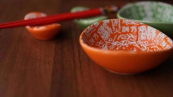 Set of ceramic dishes and red sushi sticks on wooden background photo