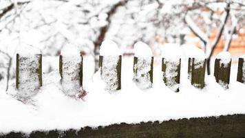 Wooden fence gate covered in white snow at heavy snowing snowstorm photo
