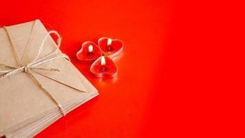 Sobres de papel kraft con velas rojas sobre fondo rojo. foto