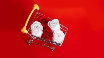 Flor de rosas rojas y blancas en carrito de compras foto