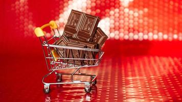 Chocolate in shopping trolley on red background. 14 february sale photo