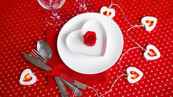 A white plate with a knife and fork on a bright red background photo