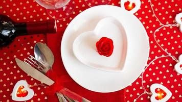 A white plate with a knife and fork on a bright red photo