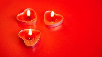 Tres velas rojas encendidas con forma de corazón. foto