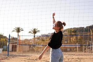 Retrato de mujer atractiva cerca de la red de voleibol en la playa. foto