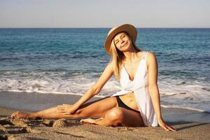 Girl in straw hat and white swim suit sitting on a sand near the sea photo