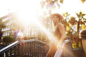 Retrato de una joven rubia con un sombrero sobre un fondo tropical foto