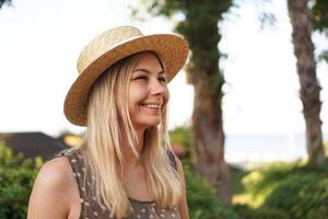Portrait of a young blonde in a hat on a tropical background photo