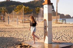 una chica en pantalones cortos y una camiseta negra en la playa cerca de la ducha. foto