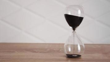 Reloj de arena de cristal con arena negra sobre mesa de madera foto