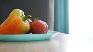 tomate y pimiento en una placa azul sobre un fondo claro en la cocina foto