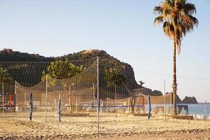cancha de voleibol en la playa de alanya, turquía. palmeras y montañas foto