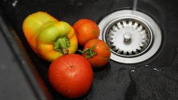 Verduras: tomates y pimientos en un fregadero de cocina negro bajo el agua foto