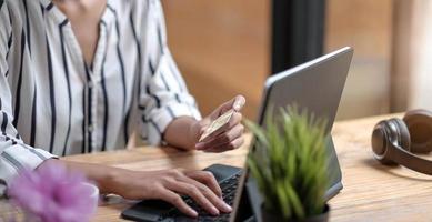 Cerrar chica en Internet en la tableta digital con tarjeta de crédito foto