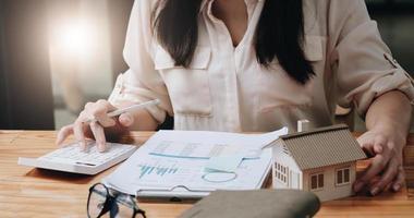Mujer cálculo financiero para comprar una propiedad con modelo de casa. foto