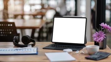Ordenador portátil con pantalla en blanco en la mesa de la cafetería. foto