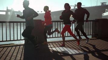 Toma de cámara lenta de personas corriendo al amanecer, filmada en phantom flex 4k video