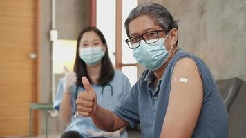 Male patient and female doctor thumb up after vaccination in home. video