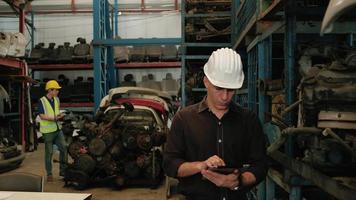 Deux ingénieurs masculins vérifiant les pièces du moteur dans un entrepôt video