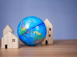 A wooden model house is placed beside a replica globe. photo