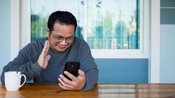 hombres asiáticos sentados y hablando en un chat de video con un teléfono inteligente. foto