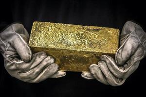 Hands holding a twenty kilogram gold ingot photo