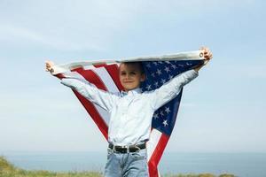 un niño sostiene una bandera de los estados unidos contra el cielo foto