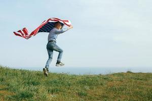 un niño corre con la bandera de los estados unidos foto