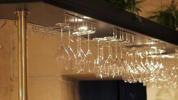 Copas de vino vacías colgando sobre un estante de madera encima de una barra video