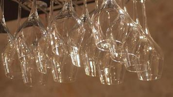 Filas de copas de vino vacías colgando sobre un estante de madera encima de una barra video