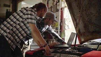 Two Mechanics in Garage Repairing a Car video