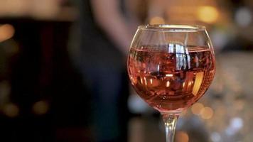una copa de vino rosado en una mesa en un bar de vinos video