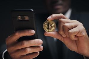 El empresario sostiene bitcoin dorado con un teléfono inteligente con gráfico comercial. foto
