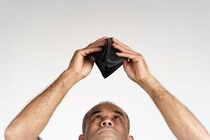 man holding upside down and looking inside his empty wallet. photo