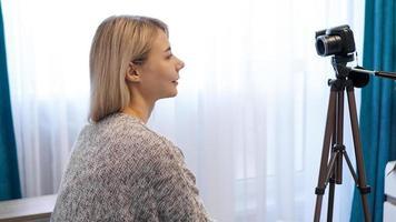 Mujer joven en ropa casual se graba a sí misma en la cámara sobre un trípode foto