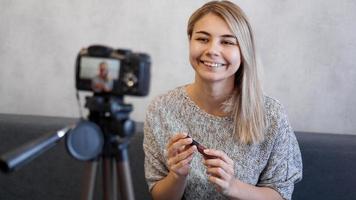 mujer vlogger mostrando lápiz labial. blogger de belleza en estudio casero foto