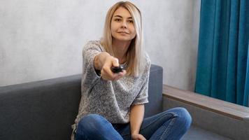 Mujer joven cambia los canales de televisión con el mando a distancia. foto