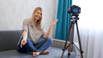 feliz bloguera contando bromas y riendo mientras graba video foto