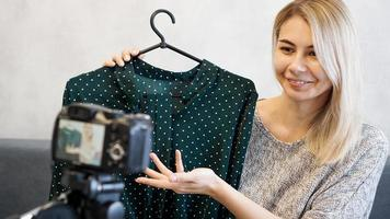 Fashion blogger recording video for blog photo