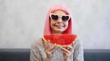 mujer con trozo de sandía. mujer lleva peluca rosa y gafas foto