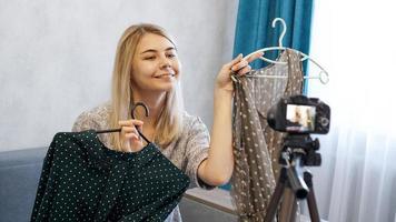bloguera de moda eligiendo su atuendo, sosteniendo dos vestidos en perchas foto