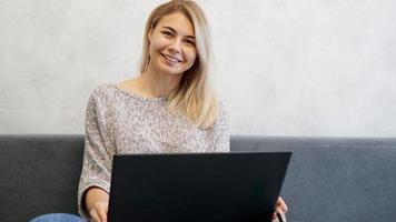 Casual young woman using laptop in living room photo