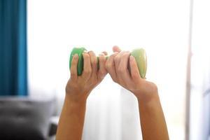 primer plano, de, mujer, utilizar, dos manos, para, sostener pesas foto