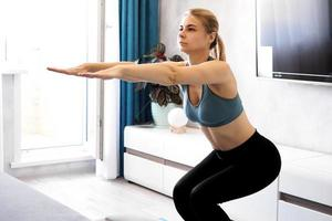 Training and lifestyle concept - woman exercising and doing squats photo
