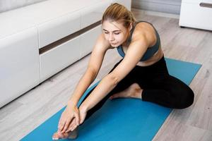 Sport, training and lifestyle concept - woman stretching leg photo