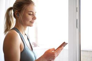 Young pretty sporty girl stands near window and listens to music photo