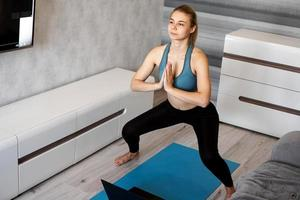 Young woman exercising and doing squats in the living room at home photo