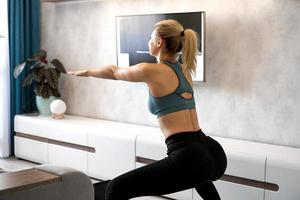 Young woman exercising and doing squats at home photo