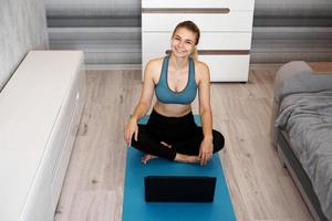 Happy young fitness woman sit on yoga mat at home near laptop photo